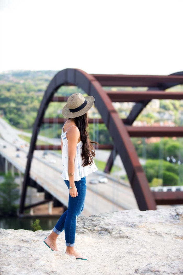 cute trendy outfits woman with long brown wavy hair wearing jeans white top hat standing on rock