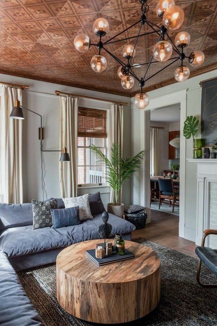 round wooden coffee table, rustic home decor, dark grey corner sofa, dark grey carpet on wooden floor