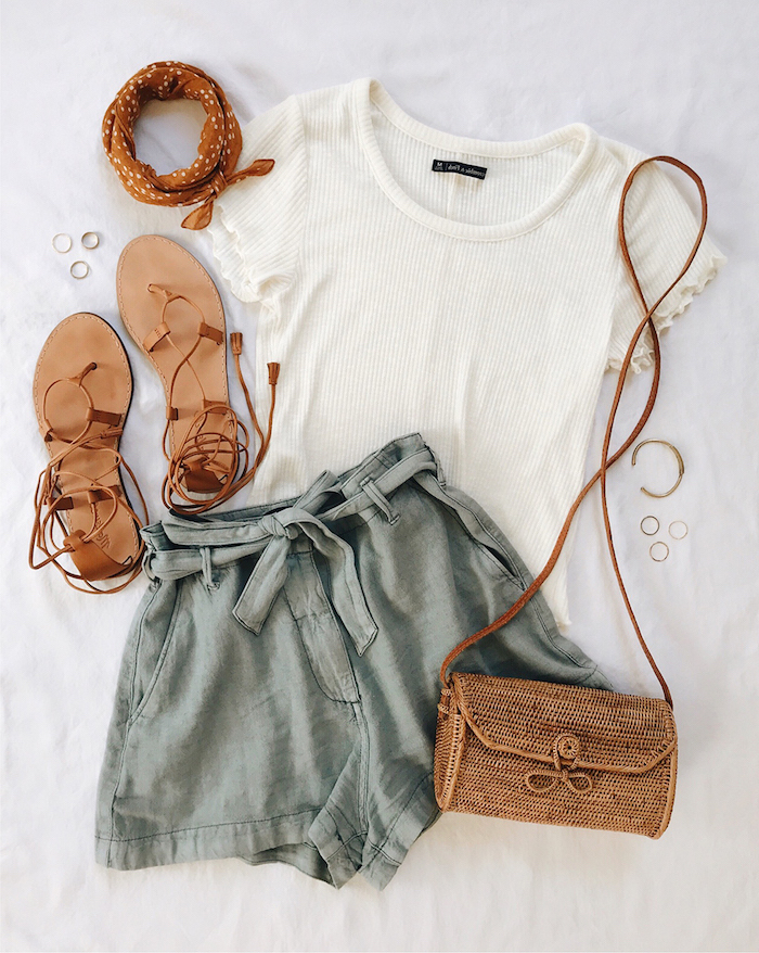 dark grey shorts white t shirt brown leather sandals bag laid out on white surface cute outfit ideas for summer