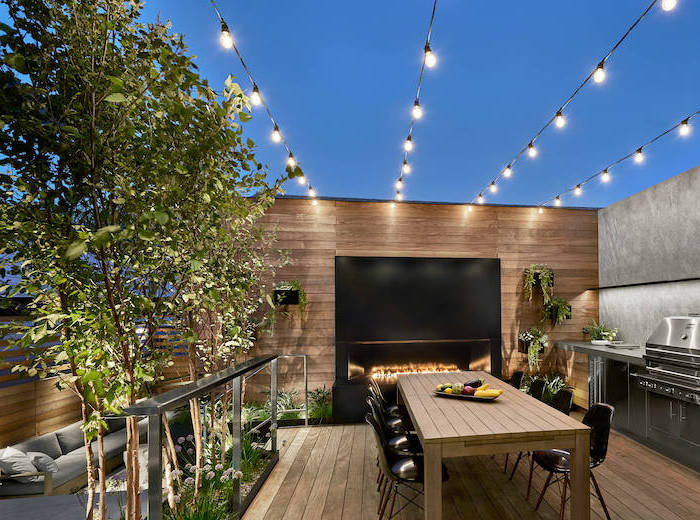 dinig table made of wood with black chairs next to fireplace outdoor bbq ideas metal kitchen cabinets with grill strings of lights hanging above