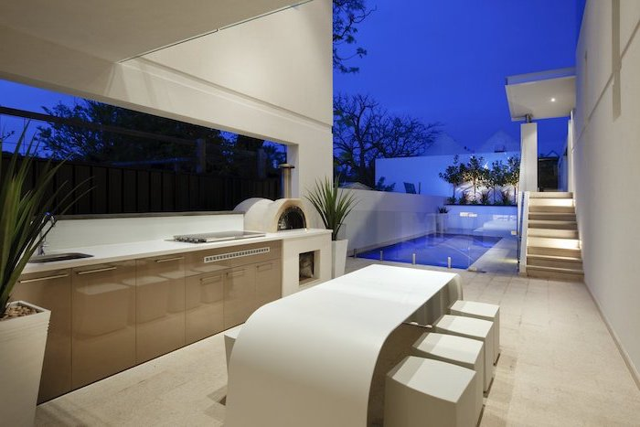 dining table and stools in white next to the pool outdoor grill station barbecue grill beige cabinets white countertops