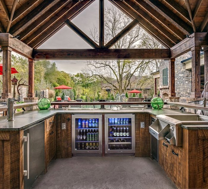 drinks fridge and wooden cabinets with marble countertop backyard kitchen ideas wooden caulted ceiling kitchen next to the pool