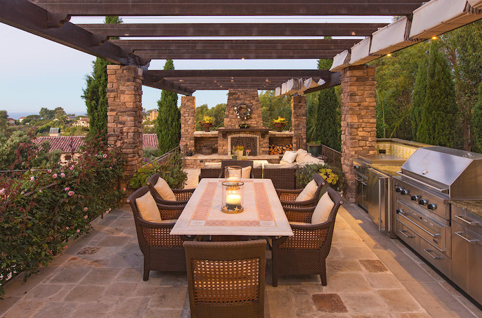 exposed wooden beams above lounge area with fireplace rustic outdoor kitchen metal cabinets and grill dining table with chairs on stone tiled floor