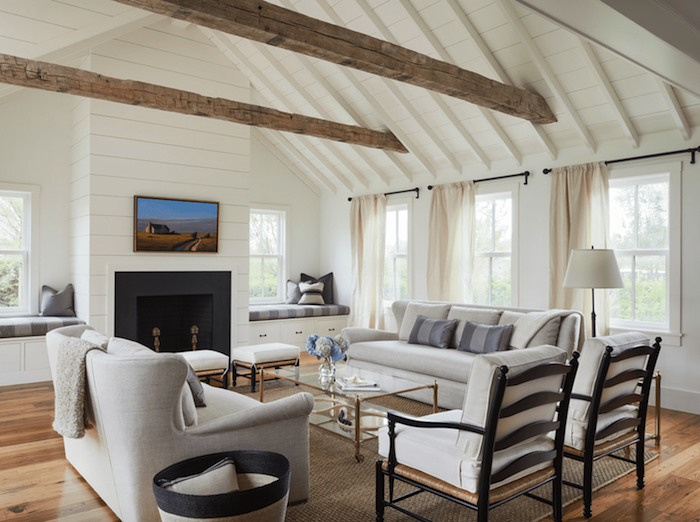 white furniture set, placed in front of a fireplace, farmhouse living room decor, glass coffee table, exposed wooden beams on white ceiling