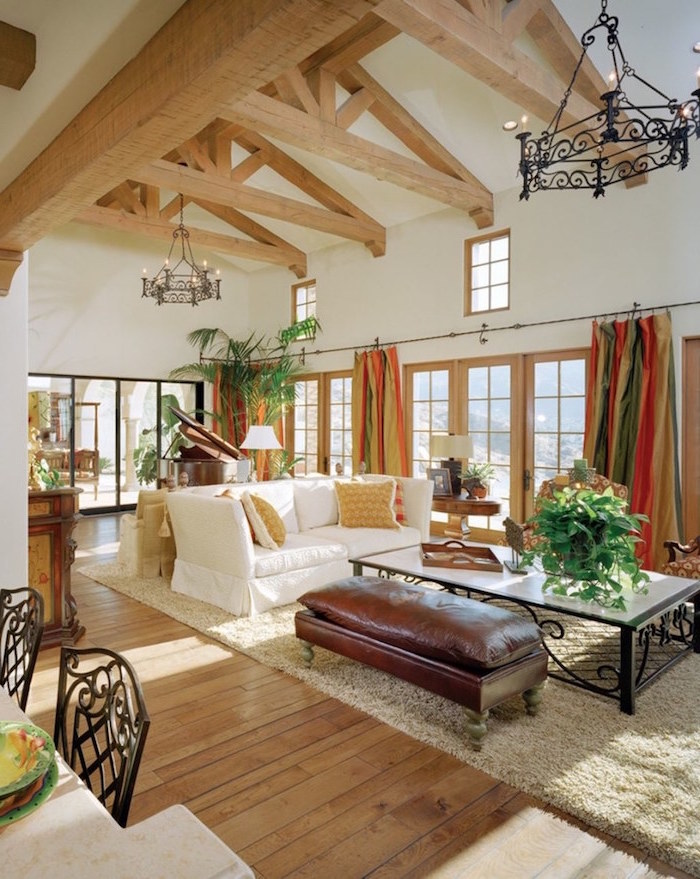 exposed wooden beams on white ceiling, farmhouse living room decor, brown leather ottoman, white sofa with throw pillows