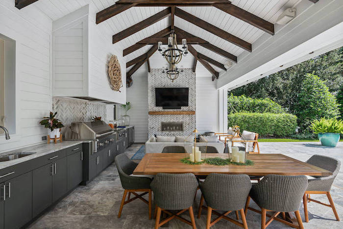 exposed wooden beams on white wooden ceiling outdoor bbq ideas lounge area with fireplace kitchen wooden dining table with eight chairs