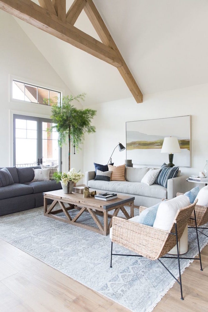 white walls, exposed wooden beams on white ceiling, farmhouse living room decor, grey and white sofas, wooden coffee table