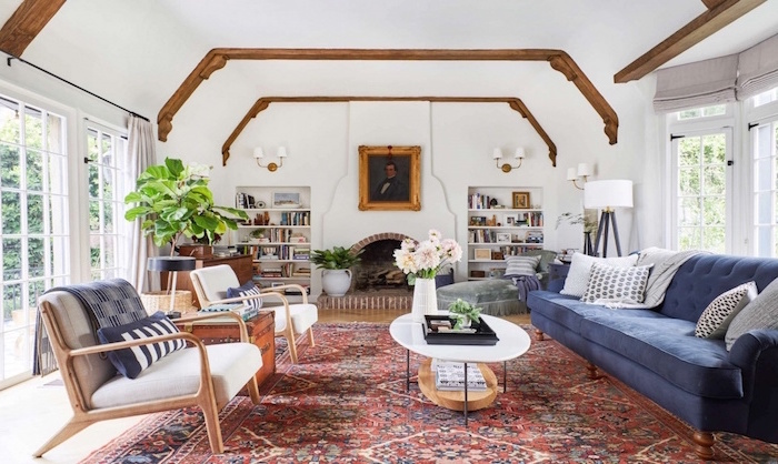 blue velvet sofa, two white armchairs, farmhouse living room ideas, colorful carpet, exposed wooden beams on white ceiling