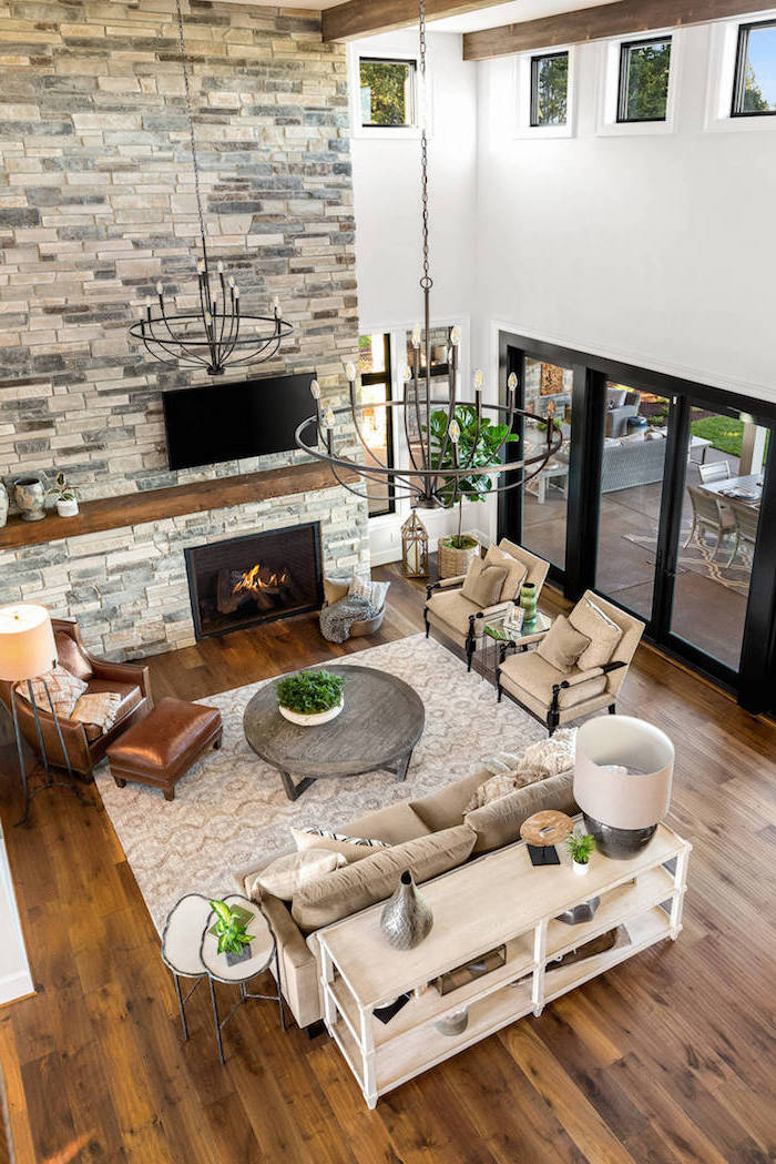 stone wall fireplace, brown leather armchair, farmhouse living room ideas, white furniture set, wooden floor