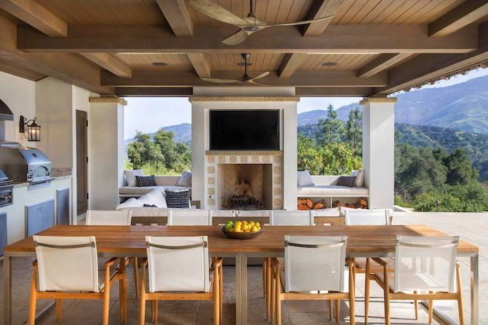 fireplace at the center large wooden dining room with chairs backyard kitchen ideas grill with cabinets