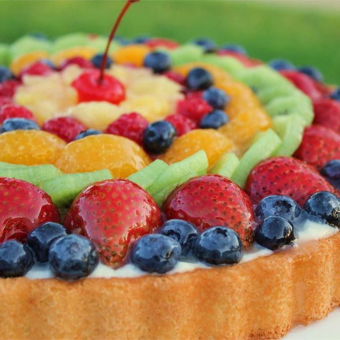 fruit cake with blueberries strawberries kiwi orange raspberries pineapple arranged in circles on top cherry in the middle easy no bake desserts