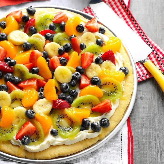 fruit pizza with oranges strawberries kiwi blueberries on top easy summer desserts placed on white plate