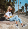 girl with long blonde wavy hair in ponytail wearing white kill bill t shirt cute summer shirts washed jeans vans sneakers