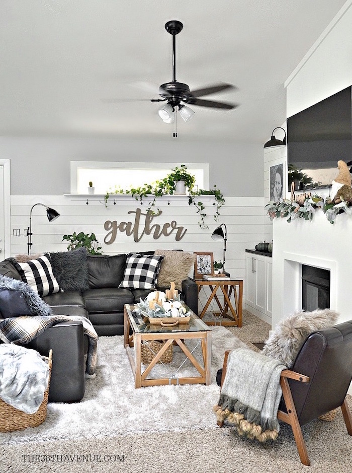 black leather corner sofa and armchair, black and white throw pillows, rustic farmhouse decor, placed in front of a fireplace