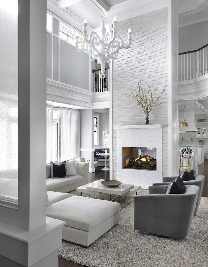 white corner sofa, two grey armchairs, placed in front of a fireplace, rustic farmhouse decor, tall white walls