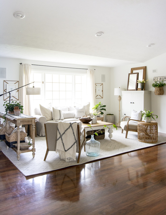 white carpet on wooden floor, rustic farmhouse decor, white sofa with grey armchairs, wooden coffee table