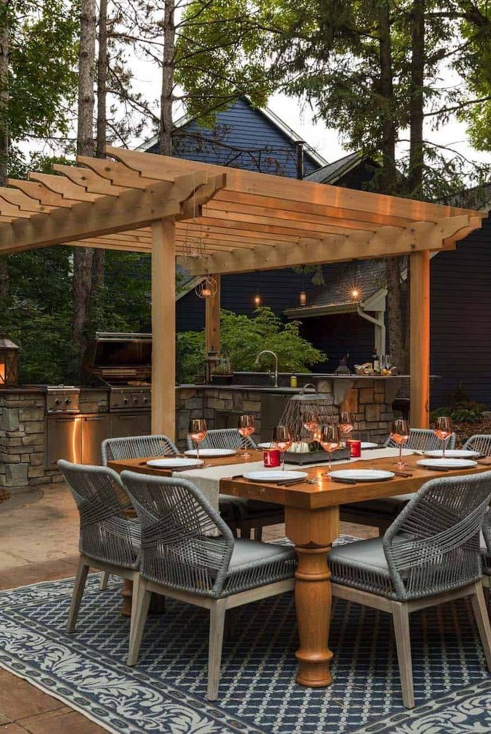 grey chairs around wooden table on grey carpet outdoor cooking station made of stone with grill cabinets sink