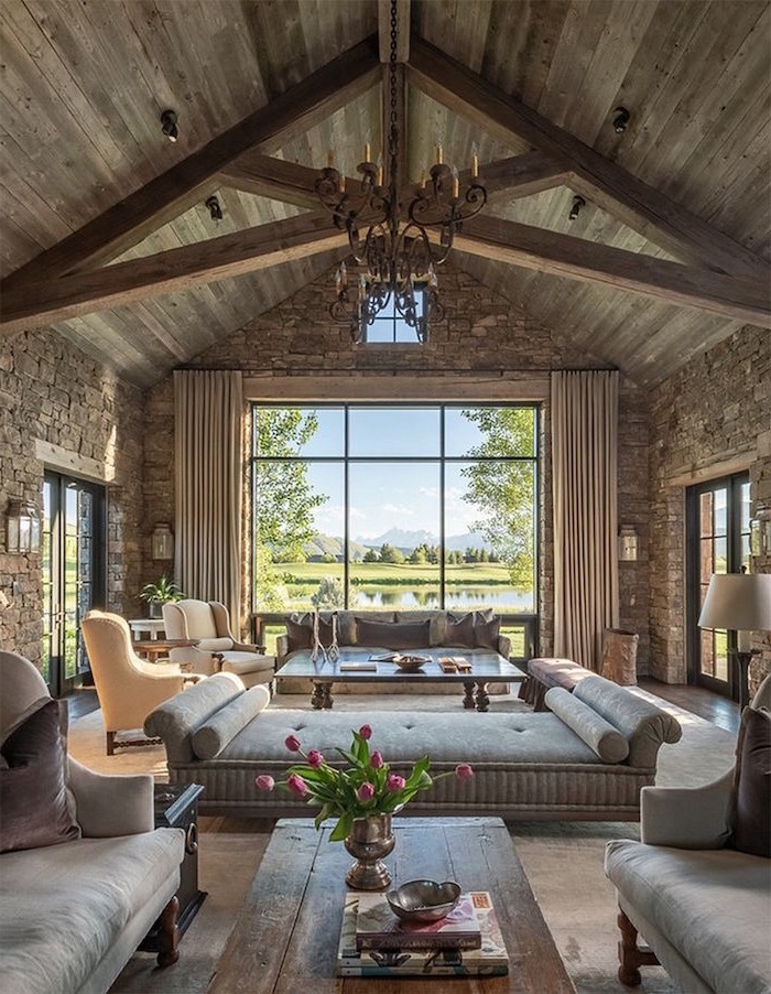 farmhouse style homes, wooden ceiling with exposed beams, grey furniture set, tall windows, stone walls