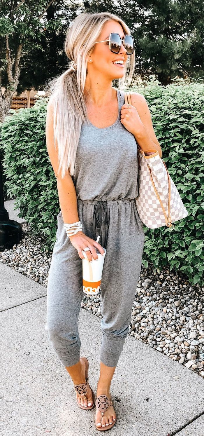 grey jumpsuit worn by blonde woman with hair in ponytail cute summer outfits wearing brown sandals and louis vuitton bag