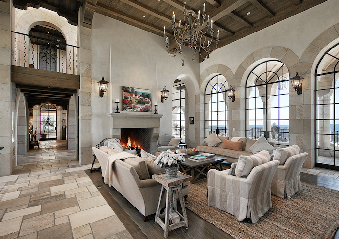 tall wooden ceiling, farmhouse style homes, white and grey furniture set, placed in front of a fireplace, tiled floor