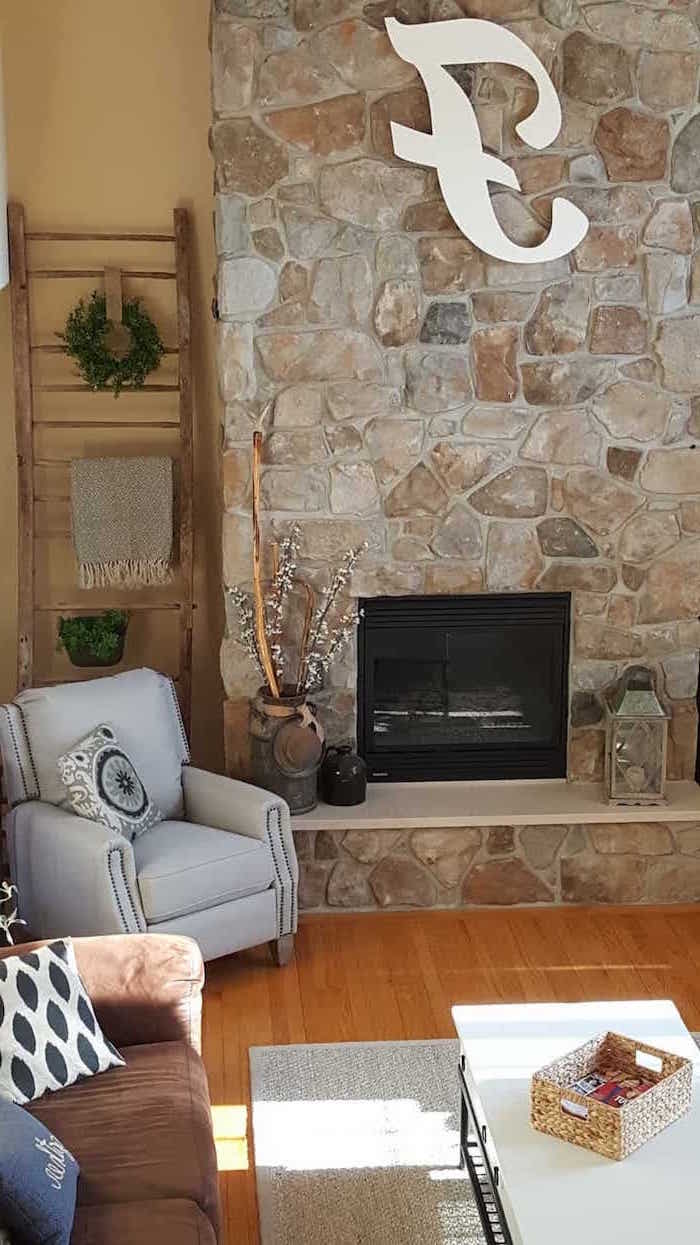 stone wall with fireplace, grey armchair, country farmhouse decor, light grey carpet on wooden floor
