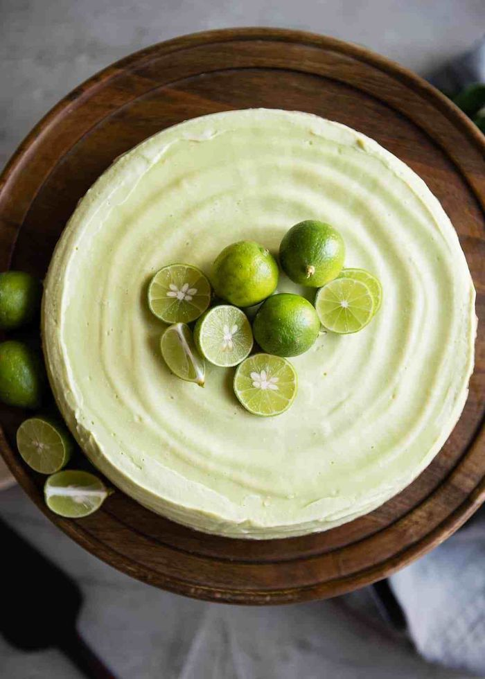key lime pie with lime slices on top and on the sides picnic desserts placed on wooden cake stand
