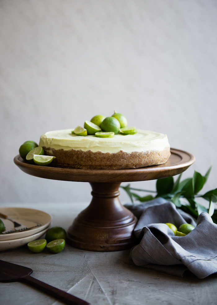 key lime tart placed on wooden cake stand picnic desserts lime slices on top and on the sides