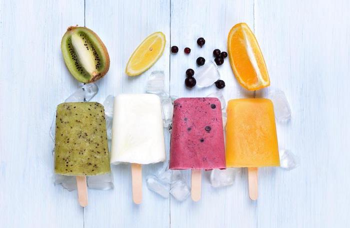 kiwi lemon blueberry orange popsicles no bake recipes arranged on white surface with ice cubes around them
