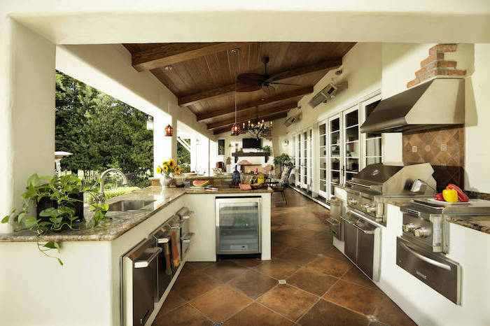 l shaped outdoor kitchen metal cabinets fridge and grill granite countertops lounge area with wooden ceiling