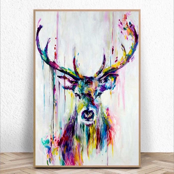 large deer, painted in different colors, painted on white background, watercolor techniques, framed and leaning on white wall