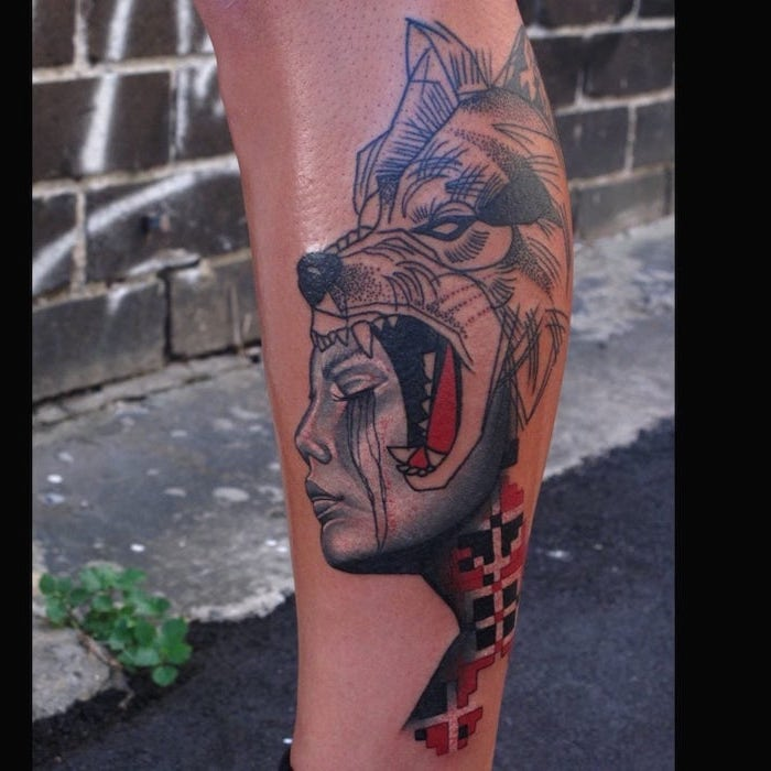 leg tattoo of female face wolf head next to it trash polka design tattooed in red and black