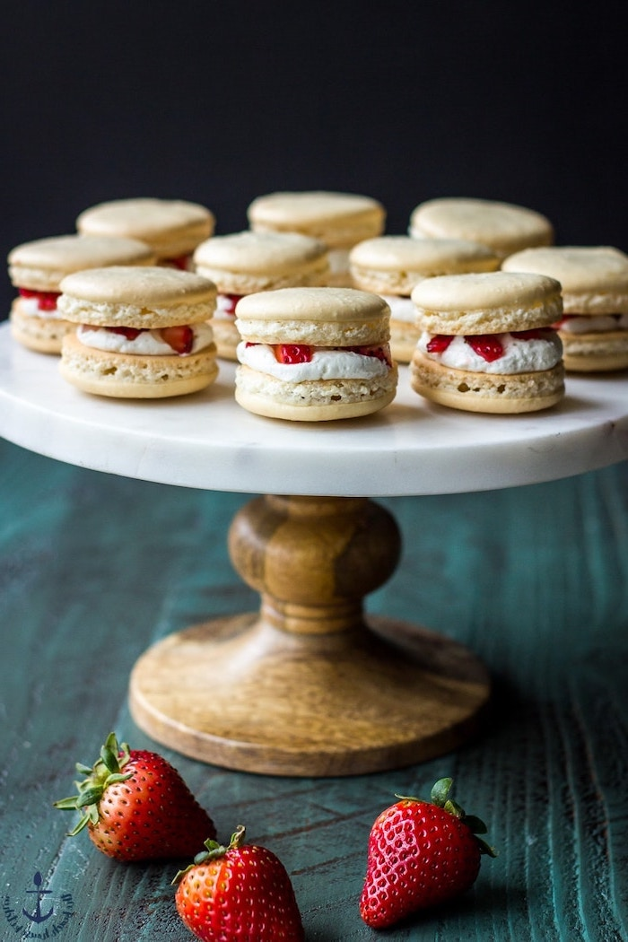 macaroons with white cream and strawberries in the middle summer dessert recipes arranged on wooden cake stand with marble surface