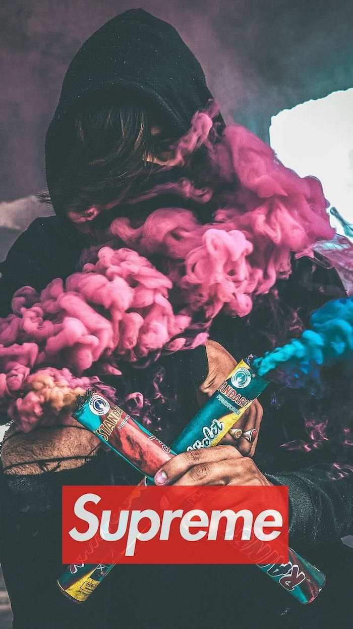 man wearing a hoodie holding to smoke cannons in pink and blue black supreme wallpaper red and white supreme logo