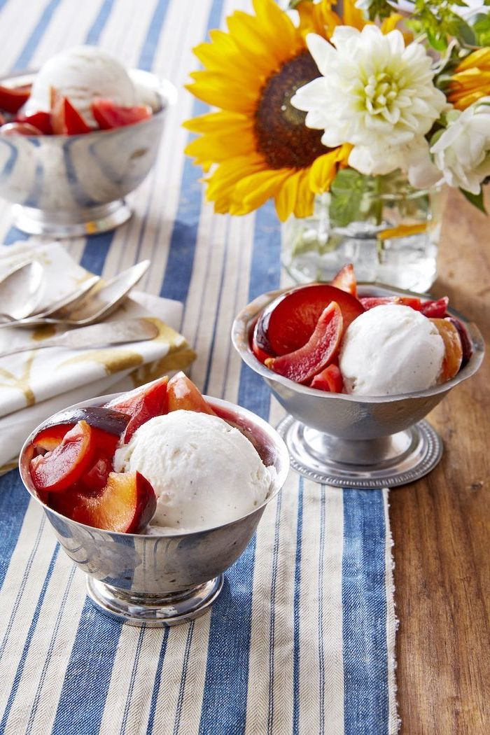 metal bowls with scoops of ice cream and marinated plums summer dessert recipes arranged on wooden table with blue and white cloth