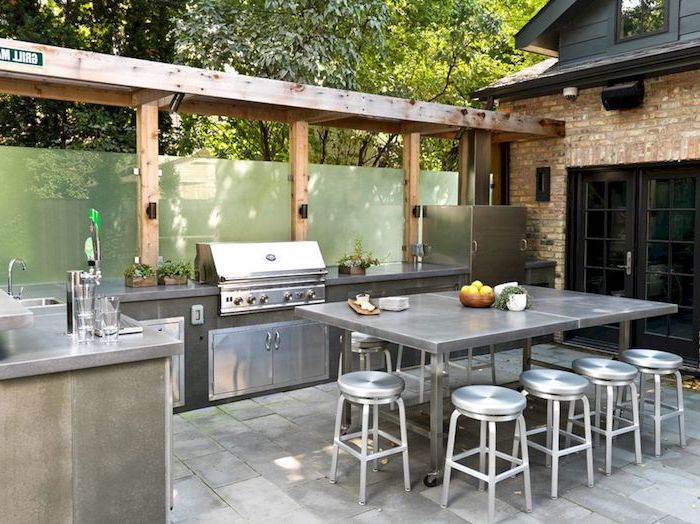 metal chairs and dining table outdoor cooking station with grill fridge sink on stone tiled floor