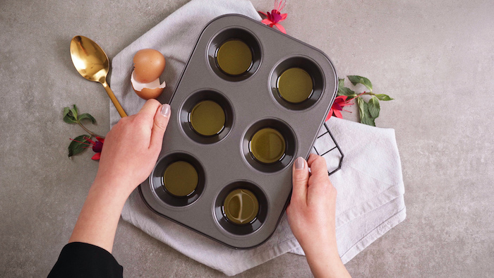muffin baking tray each space filled with oil on the bottom fruit desserts recipes placed on white cloth on grey surface
