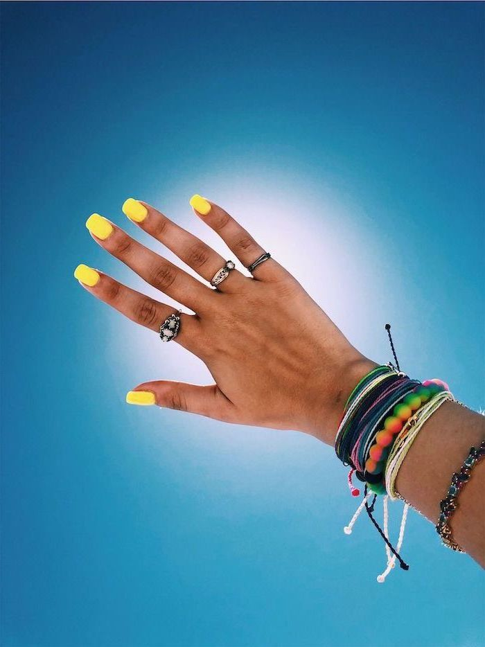 yellow nail polish, medium length square nails, blue background, bracelets on the hand, cute nail ideas