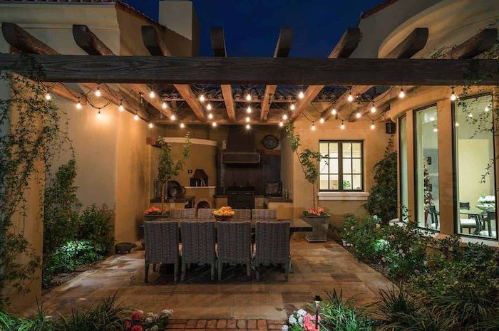 outdoor grill station fireplace and cabinets tiled floor large dining table with eight chairs strings of lights wrapped around wooden beams