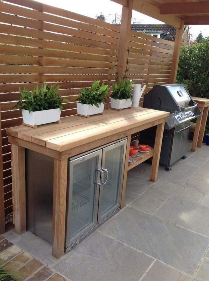 outdoor kitchen ideas wooden table with fridge and barbecue grill three potted plants on top stone tiles on the floor