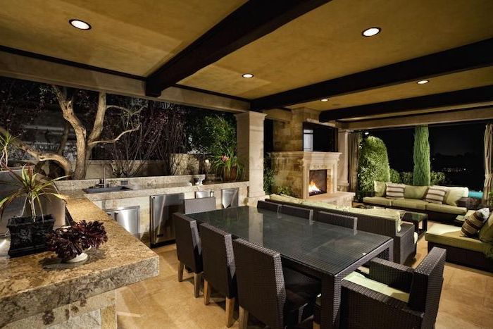 outdoor lounge are with stone countertops large sofas outdoor kitchen ideas dining table chairs fireplace