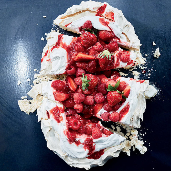 pavlova cake with strawberries on top no bake recipes cut into slices on dark surface