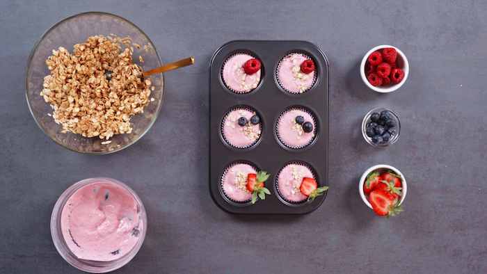 picnic desserts muffin tray with frozen skyr cupcakes ingredients in bowls on the sides on grey surface