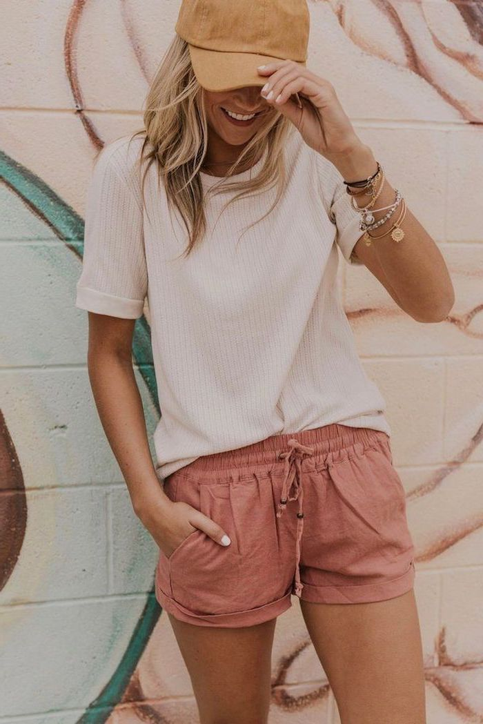 pink short white t shirt worn by blonde woman summer outfits lots of bracelets and beige cap