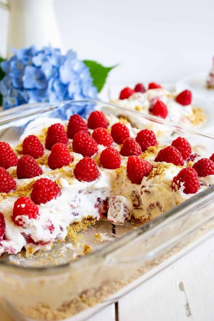 raspberry cheesecake inside glass baking tray summer desserts placed on white wooden surface