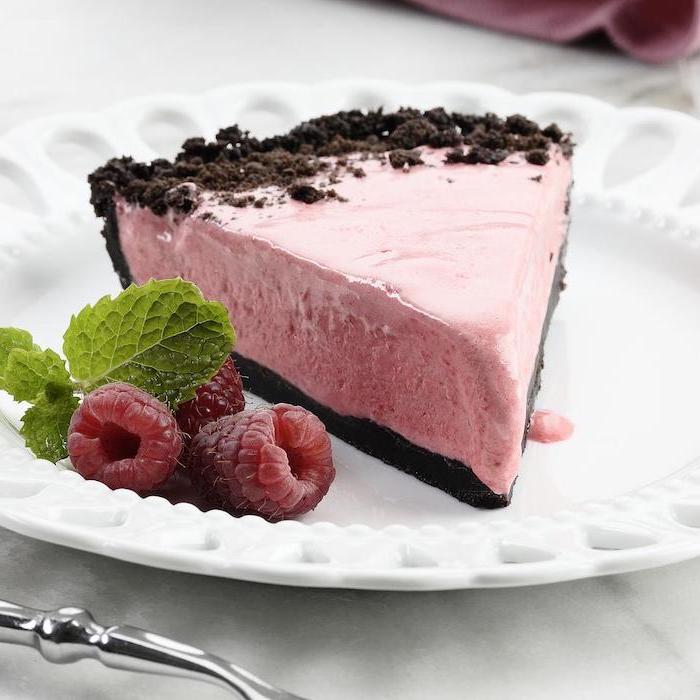 raspberry chocolate cheesecake placed on white plate cookie crumbs on top summer desserts raspberries mint leaves on the side
