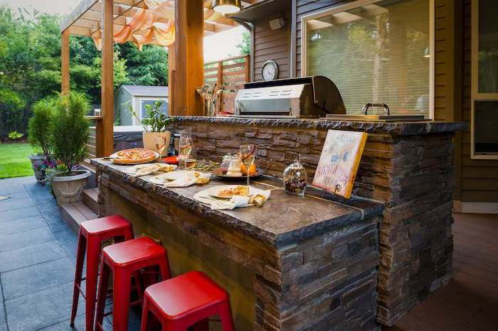 red bar stools next to kitchen island made of stone with granite countertops outdoor bbq ideas built in grill