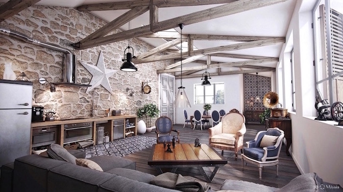 stone accent wall, exposed wooden beams on white ceiling, modern farmhouse interior, grey corner sofa, open plan living room and kitchen