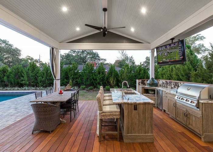 rustic outdoor kitchen next to the pool vaulted ceiling wooden floor cabinets and kitchen island with marble countertops long dining table