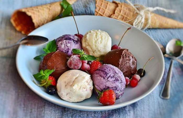 scoops of different ice cream flavors arranged on plate no bake recipes garnished with berries cherries and mint leaves