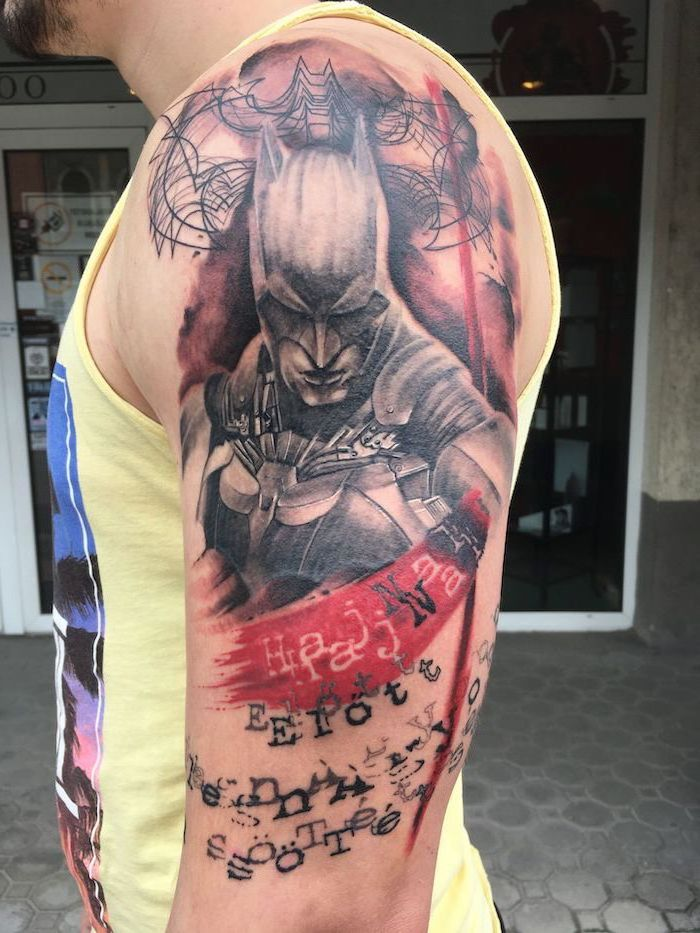 shoulder tattoo of batman trash polka tattoo words written underneath on man wearing yellow top
